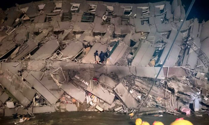 Rescuers try to enter an office building that collapsed on its side after an early morning earthquake in Tainan, southern Taiwan, on Feb. 6, 2016. A 6.4-magnitude earthquake struck southern Taiwan, according to the U.S. Geological Survey. (AP Photo)