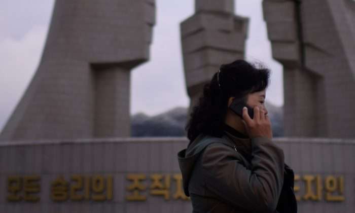"""A woman talks on a mobile phone before the """"Monument to Party Founding"""" in Pyongyang on Oct. 11, 2015. (Ed Jones/AFP/Getty Images)"""
