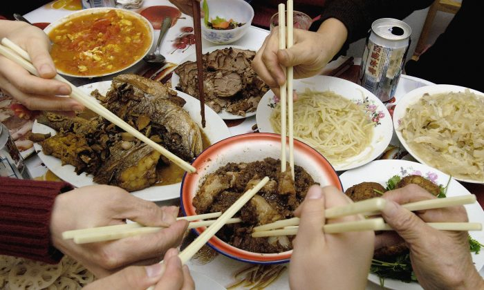 A Chinese family eat their New Year's Eve Dinner in Beijing, China, on Feb. 8, 2005. (China Photos/Getty Images)