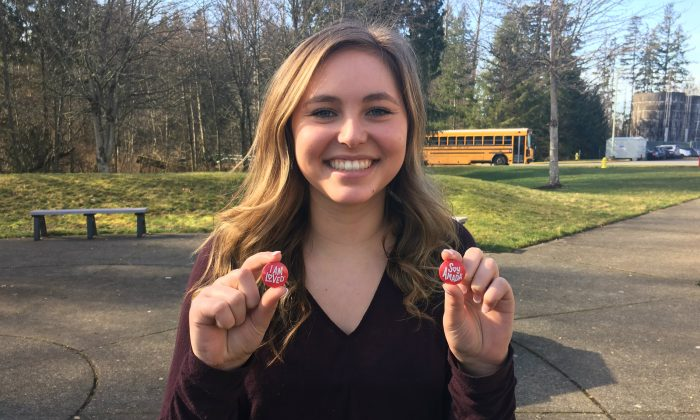 """Sophie Hunter holds """"I am loved"""" buttons handed out to freshmen through a Random Acts of Kindness club initiative. (Courtesy of Cedarcrest High School)"""