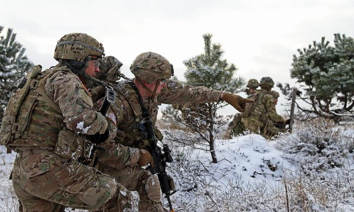 Army Spc. Ethan Mitchell (R) points out an objective to Army Spc. Raymon Najera during a live-fire exercise in Konotop, Poland, on Jan. 18. The U.S. military is increasing its presence in Europe, to counter increased aggression from Russia. (Sgt. Paige Behringer/U.S. Army)