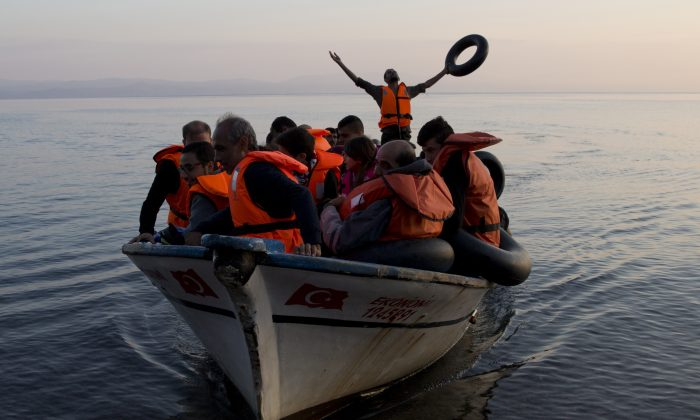 Syrian refugees arrive from Turkey on the shores of the Greek island of Lesbos, aboard a fishing boat, on Sept. 27, 2015. (AP Photo/Petros Giannakouris)