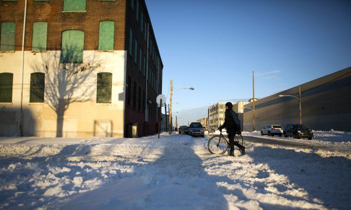 A man walks his bike down an snowy street in the Fishtown neighborhood on January 24, 2016 in Philadelphia, Pennsylvania. (Jessica Kourkounis/Getty Images)