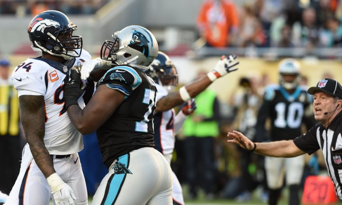 Michael Oher (C) of the Carolina Panthers struggled blocking DeMarcus Ware (L) at times during Super Bowl 50 as he sometimes had trouble with the field. (Timothy A. Clary/AFP/Getty Images)