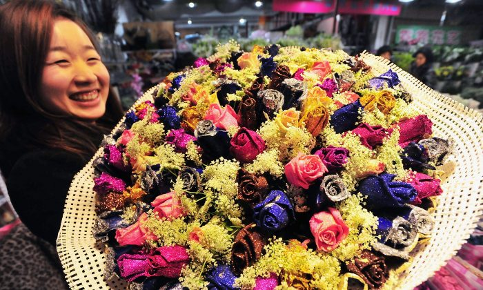 A woman poses with a bouquet of roses at a flower market in China as Valentine's Day approaches in this file photo. (ChinaFotoPress/Getty Images)