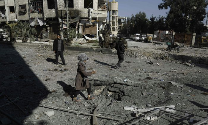 A Syrian girl makes her way through debris following reported air strikes in Hammuriyeh on the outskirts of the capital Damascus, on Feb. 12. The civil war in Syria is escalating ahead of a planned ceasefire. (Abdulmonam Eassa/AFP/Getty Images)