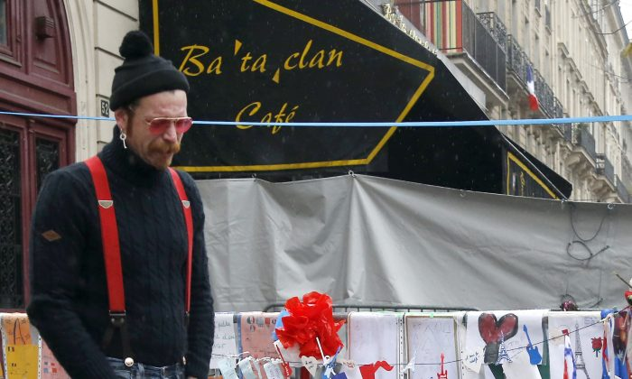 Jesse Hughes of the band Eagles of Death Metal pays his respects to 89 victims who died in a Nov. 13 attack, at the Bataclan concert hall in Paris, France, Tuesday, Dec. 8, 2015. Members of the California rock band Eagles of Death Metal are back at the ravaged Paris theater where they survived a massacre by Islamic extremist suicide bombers. (AP Photo/Jacques Brinon)