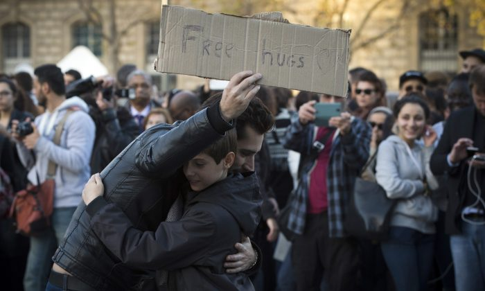 A man offers free hugs at the Place de la Republique in Paris, on Nov. 15, 2015. (JOEL SAGET/AFP/Getty Images)