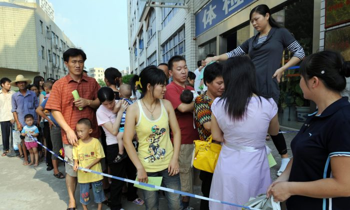 Parents accompanying their children for a check-up queue up in front of Longgang central hospital in Shenzhen, in southern China's Guangdong province on September 21, 2008. (TED ALJIBE/AFP/Getty Images)