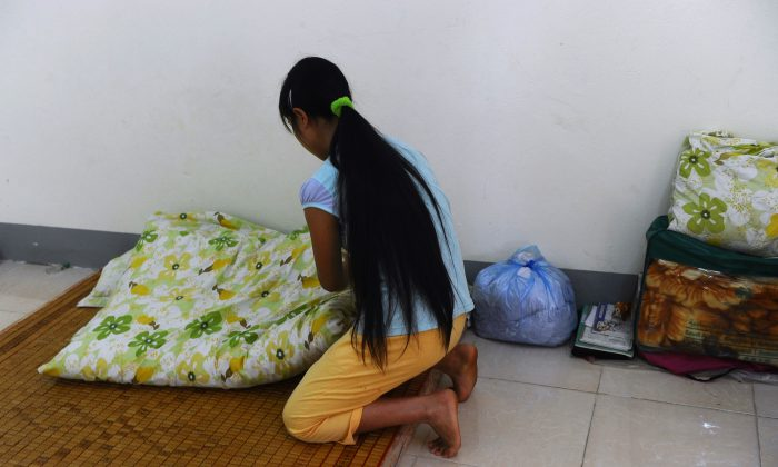 This picture taken on May 9, 2014 shows H'mong ethnic girl arranging her bed at a centre for trafficked women. When she turned 16, her brother promised to take her to a party in a tourist town in northern Vietnam. Instead, he sold her to a Chinese family as a bride. (HOANG DINH NAM/AFP/Getty Images)