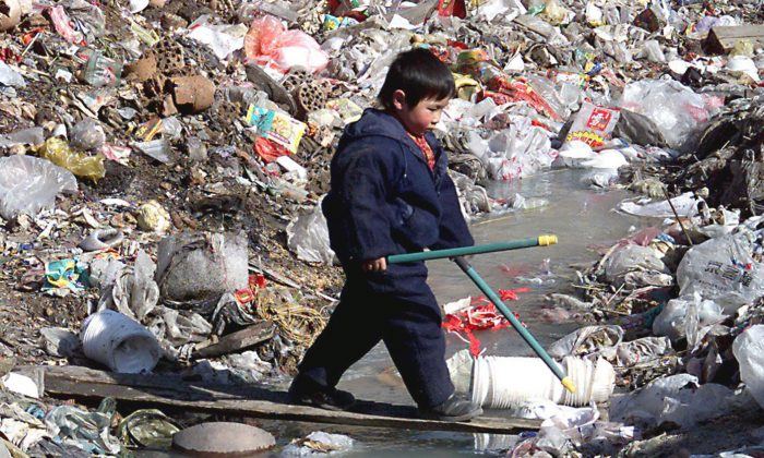 A young boy carefully walks on a thin board across a heavily polluted stream and  trash dump outside his family's old courtyard house in Beijing on Feb. 16, 2000. Experts at China Geological Survey, a state-led research institute, said at a conference in 2010 that 90% of China's underground water sources are polluted to one degree or another, while 60% are seriously polluted. (Stephen Shaver/AFP/Getty Images)