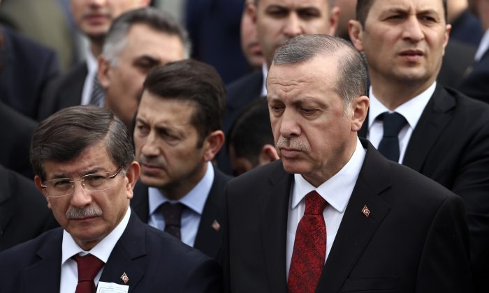 Turkey's President Recep Tayyip Erdogan, right, and Prime Minister Ahmet Davutoglu, left, arrive to attend funeral prayers for army officer Seckin Cil, who was killed in Sur, Diyarbakir Wednesday, in Ankara, Turkey, Thursday, Feb. 18, 2016. Six soldiers were killed after PKK rebels detonated a bomb on the road linking the cities of Diyarbakir and Bingol in southeastern Turkey as their vehicle was passing by, according to Turkey's state-run Anadolu Agency. The deaths come a day after a suicide bombing claimed the lives of at least 28 people and wounded dozens of others.(AP Photo/Burhan Ozbilici)