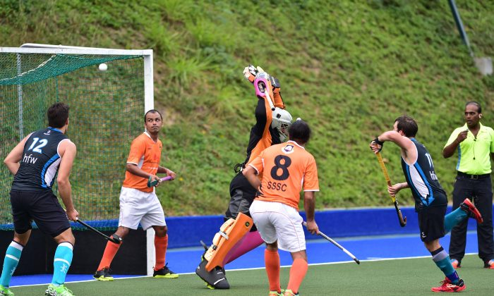 Angus Allan (Blue No 11) scores for HK Football Club against SSSC in the HKHA Premier Division match at King's Park on Sunday Feb 14, 2016. (Bill Cox/Epoch Times)