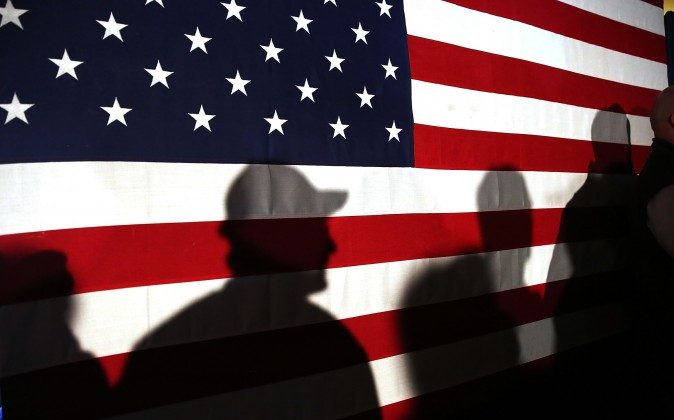 Shadows are reflected on an American Flag as people line up to speak with Ohio Governor and Republican presidential candidate John Kasich  on Feb. 11, 2016, in Myrtle Beach, S.C. (Spencer Platt/Getty Images)