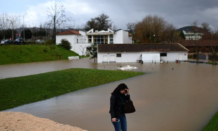 A woman walks on an improvised dike in a flooded area in Coimbra, central Portugal, on February 14, 2016. (FRANCISCO LEONG/AFP/Getty Images)