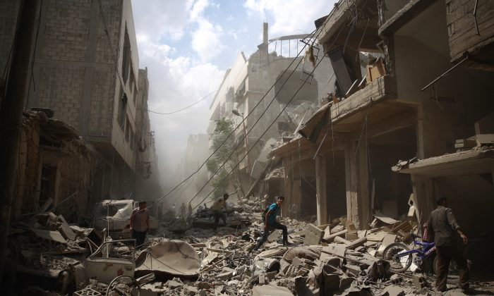 Syrians walk amid the rubble of destroyed buildings following reported airstrikes by regime forces in Douma, east of the capital Damascus, on Aug. 30, 2015. More than 260,000 people have been killed since Syria's conflict began in March 2011, and millions have been displaced by the war. (Abd Doumany/AFP/Getty Images)