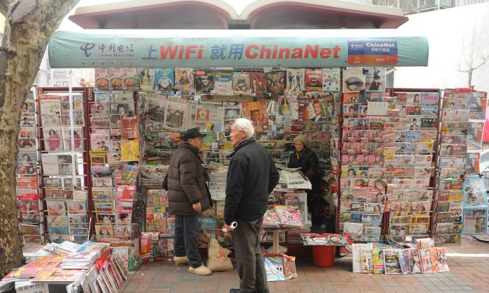 A newspaper vendor talks to customers at her booth on a street in Shanghai on Jan. 8, 2013.  (Peter Parks/AFP/Getty Images)
