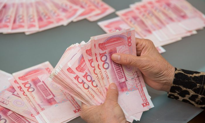 A woman counts Chinese yuan bills worth thousands of dollars in Vancouver, Canada, on Oct. 27, 2015. (Benjamin Chasteen/Epoch Times)