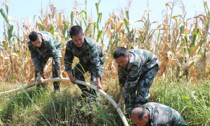 Soldiers help villagers pump water from a pond at Pingdi village on July 31, 2013 in Loudi, China. (ChinaFotoPress/Getty Images)