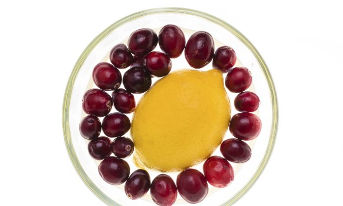 Fresh cranberries floating around a lemon in a small glass bowl (MLRamos/iStock)