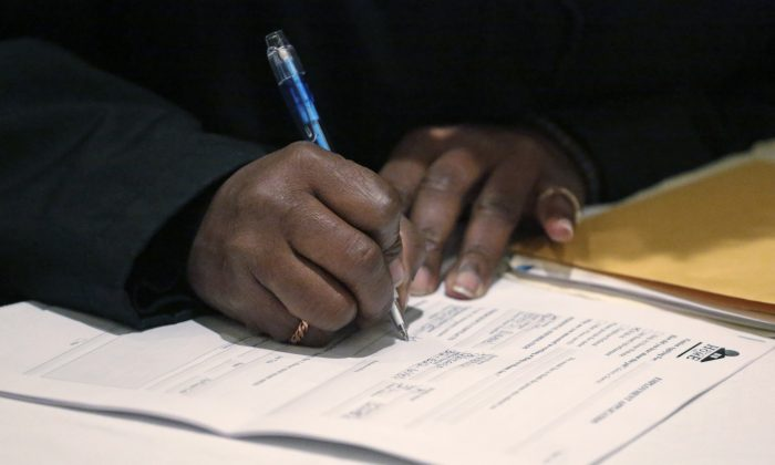 A job seeker fills out an application during a National Career Fairs job fair in Chicago on April 22, 2015. (AP Photo/M. Spencer Green)