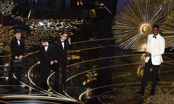Actor Chris Rock presents children representing accountants from PricewaterhouseCoopers on stage at the 88th Oscars on Feb. 28, 2016 in Hollywood, California. (Mark Ralston/AFP/Getty Images)