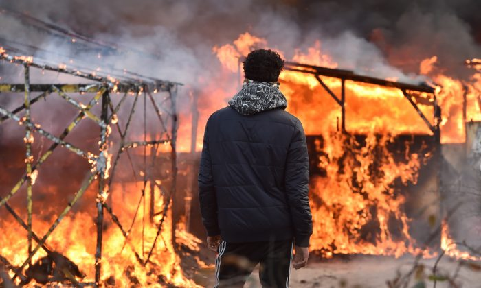 "A migrant looks at shacks burning during the dismantling of half of the ""Jungle"" migrant camp in the French northern port city of Calais, on February 29, 2016. Clashes broke out between French riot police and migrants on February 29 as bulldozers moved into the grim shantytown on the edge of Calais known as the ""Jungle"" to start destroying hundreds of makeshift shelters. AFP PHOTO / PHILIPPE HUGUEN / AFP / PHILIPPE HUGUEN        (Photo credit should read PHILIPPE HUGUEN/AFP/Getty Images)"