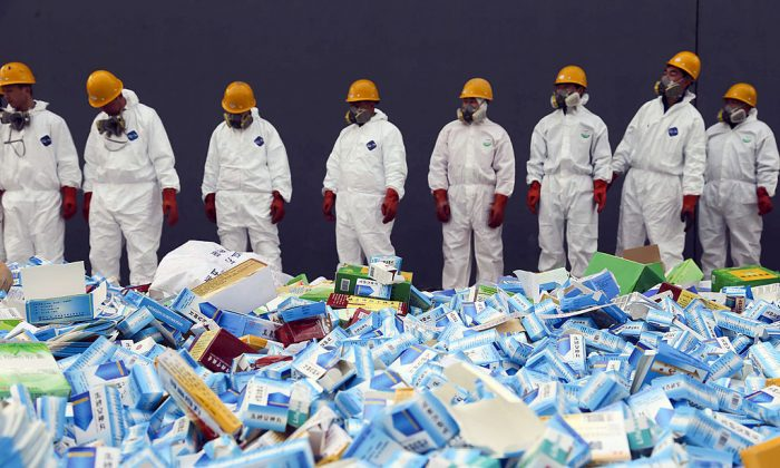 Health workers prepare to destroy fake medicines seized in Beijing on March 14, 2013. A man in Shandong survives after taking 200 fake sleeping pills. (STR/AFP/Getty Images)