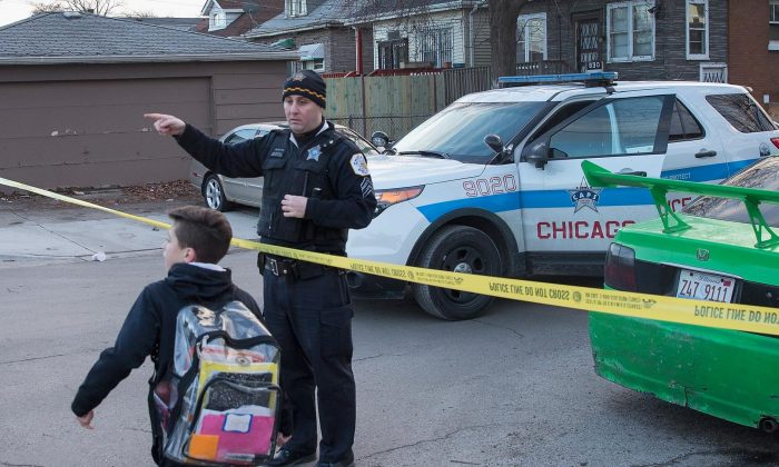 A Chicago police officer directs a boy walking home from school around the perimeter of a crime scene where six people were found slain inside a home in Chicago on Feb. 4, 2016. (Scott Olson/Getty Images)