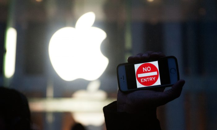 """A protester holds up an iPhone that reads """"No Entry"""" outside of the the Apple store on 5th Avenue in New York City on Feb. 23. While Apple claims to support user privacy in the United States, it has cooperated closely with authorities in China. (Bryan Thomas/Getty Images)"""