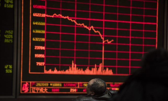 Investors watch stock prices on screens at a securities company in Beijing on Feb. 25, 2016. Chinese stocks and emerging market currencies are a sea of red for 2018 because of U.S. dollar liquidity tightening. (Fred Dufour/AFP/Getty Images)