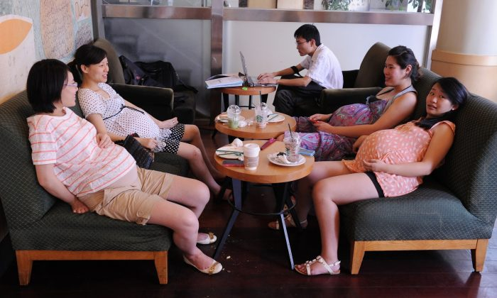 Four pregnant women relax in a coffee shop during a support group meeting at a shopping center in Shanghai on July 30, 2011. (MARK RALSTON/AFP/Getty Images)