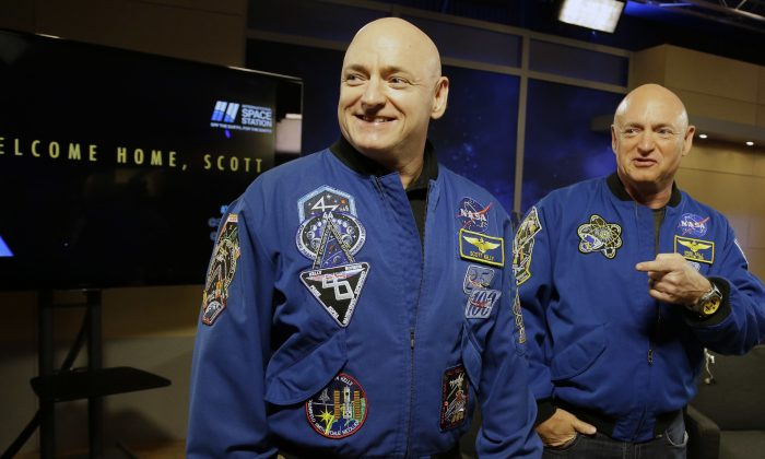 NASA astronaut Scott Kelly, left, and his twin Mark get together before a press conference Friday, March 4, 2016, in Houston. Scott Kelly set a U.S. record with his a 340-day mission to the International Space Station. (AP Photo/Pat Sullivan)