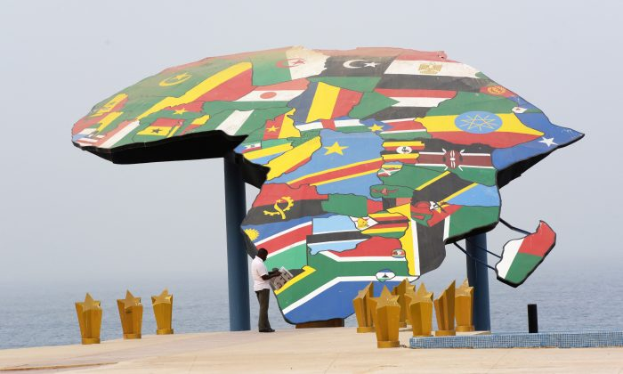 A man reads his newspaper in front a map of Africa at the Place du Souvenir Africain, in Dakar, on Jan. 27, 2016. (Seyllou/AFP/Getty Images)