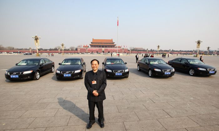 The delegate Li Shufu, chairman of China's Geely Holding Group in front of Volvo cars on the Tiananmen Square, China  on March 5, 2011. (Feng Li/Getty Images)