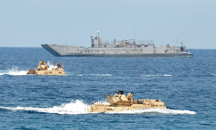 Amphibious assault vehicles of the U.S. Marines speed past a landing ship during an amphibious landing exercise on a beach at San Antonio in Zambales province on April 21, 2015. The exercise was part of the annual Philippine-US joint maneuvers some 137 miles east of the Scarborough Shoal in the South China Sea. (Ted Aljibe/AFP/Getty Images)