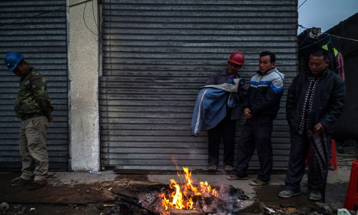 Workers keep warm next to a bonfire at a demolished industrial area at Houjie town in Dongguan, China, on Jan. 26. (Lam Yik Fei/Getty Images)