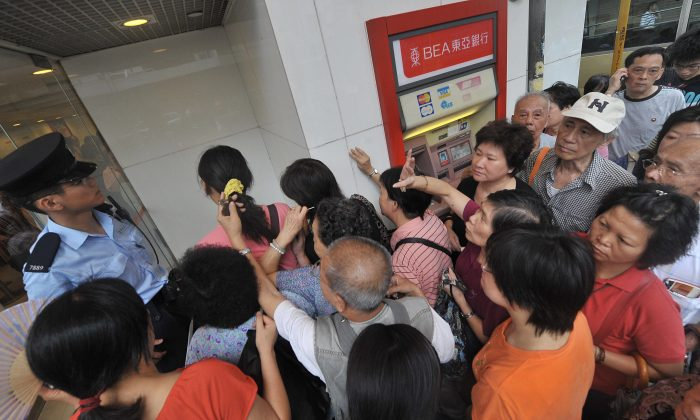 A policeman (L-in blue shirt) tries to assist customers as they crowd the entrance of a branch of Hong Kong's Bank of East Asia (BEA) on September 24, 2008. (MIKE CLARKE/AFP/Getty Images)