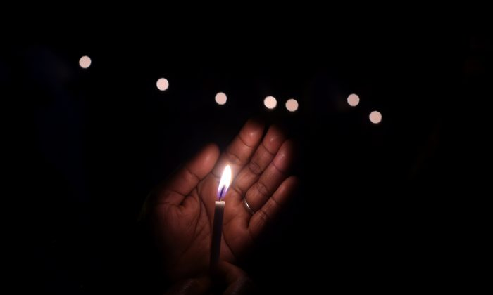 An Indian demonstrator holds a candle as she takes part in a vigil and silent protest against the alleged gang-rape of a nun in the eastern state of West Bengal, and attacks on Churches in Pakistan and India, in New Delhi, on March 16, 2015. Hundreds of priests, school girls, and other protesters staged a peaceful rally March 16, 2015, in the Indian city of Kolkata to support an elderly nun who was gang-raped at her convent school. (Sajjad Hussain/AFP/Getty Images)