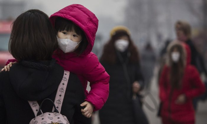 A Chinese girl wears a mask to protect against pollution as she is carried in a shopping district in heavy smog in Beijing, China, on Dec. 8, 2015. (Kevin Frayer/Getty Images)