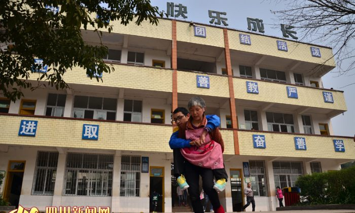 Xu Guowen carries her son Luo Yu at school. (Sichuan News Net)