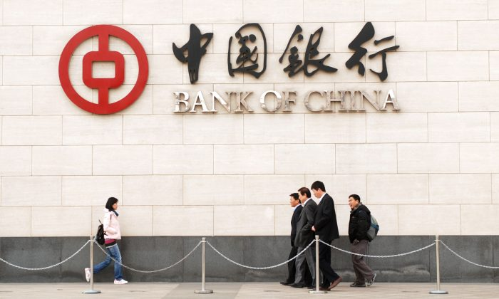 Pedestrians walking past the Bank of China in Beijing on Dec. 14, 2009. (Wang Zhao/AFP/Getty Images)