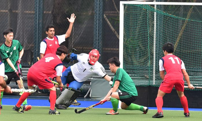 Goalmouth action between Hong Kong (in red) and Macau in the senior Interport hockey fixture at King's Park on Sunday March 6, 2016. (Bill Cox/Epoch Times)