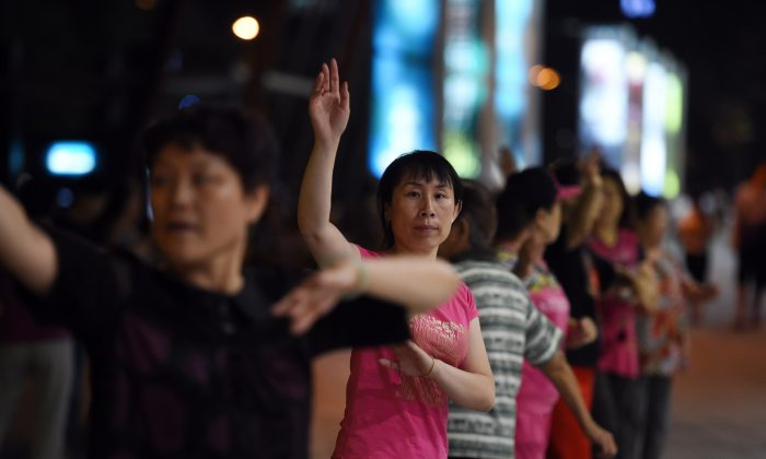 A group of women dance in front of a shopping mall near a residential compound in Beijing on September 7, 2015. (GREG BAKER/AFP/Getty Images)