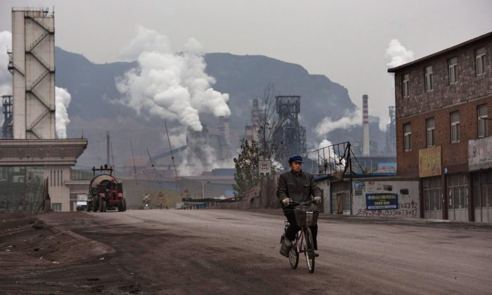 A Chinese worker rides his bike as smoke billows from a nearby steel factory on Nov. 19, 2015 in the Hebei Province, China. (Kevin Frayer/Getty Images)