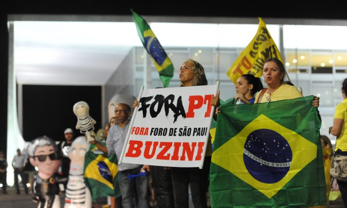 """Demonstrators protest against former president Luis Inacio """"Lula"""" da Silva and his Workers' Party (PT) in front of Planalto Palace in Brasilia on March 4, 2016. Both Lula and his successor Dilma Roussef have been marred with corruption. (Andressa Anholete/AFP/Getty Images)"""