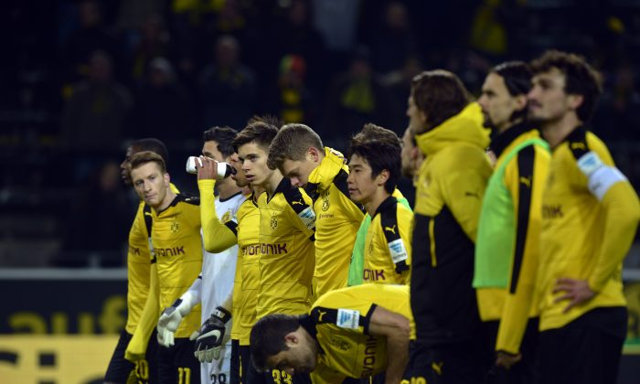 Dormund's players line up to show their respects after the death of a fan during the German first division Bundesliga football match Borussia Dortmund versus Mainz in Dortmund. (Sascha Schuermann/AFP/Getty Images)
