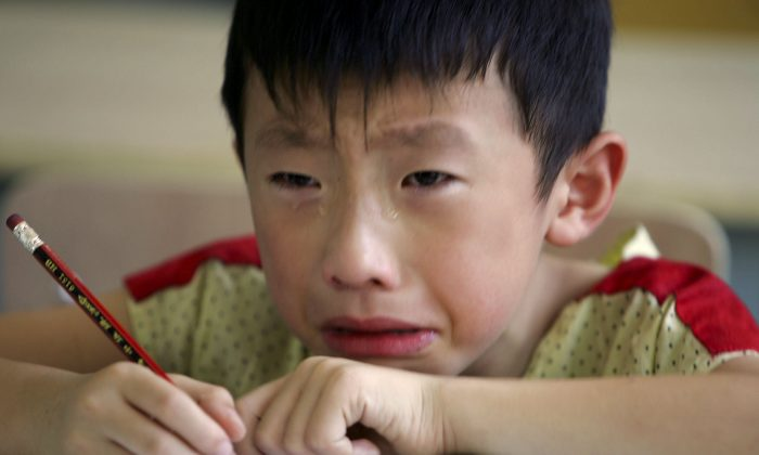 A boy cries during class because he misses his mother at the West Point Training Center August 2, 2006 in Hangzhou, Zhejiang Province, China. (Cancan Chu/Getty Images)