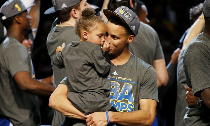 Stephen Curry of the Golden State Warriors celebrates with his daughter Riley after defeating the Cleveland Cavaliers in Game Six of the 2015 NBA Finals. (Ezra Shaw/Getty Images)