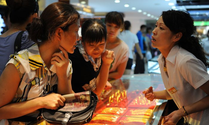 Customers look at gold jewellery on display at a shop in Hefei, east China's Anhui province on August 23, 2010. (STR/AFP/Getty Images)